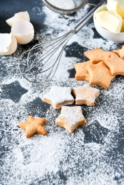 Christmas cookies in the shape of stars, on a dark background of stars and powdered sugar, ingredients for cookies butter, sugar, flour. preparation for Christmas 2019 and new year 2019